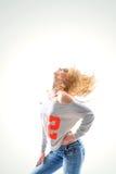Belle blonde de jeune femme dans le T-shirt et des jeans sur le backg blanc Photographie stock libre de droits