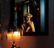 Belle blonde regardant elle-même dans un miroir photos stock