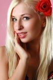 Belle blonde sexy avec la fleur rouge dans le cheveu Photographie stock libre de droits