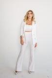 Belle blonde sexy dans un costume blanc posant sur le fond blanc Image stock