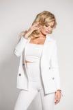 Belle blonde sexy dans un costume blanc posant sur le fond blanc Images libres de droits