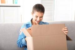 Belle boîte d'ouverture de jeune femme avec le colis tout en se reposant sur le sofa à la maison image libre de droits