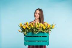 Belle boîte femelle de participation de jardinier avec des tulipes sur le fond bleu photo stock