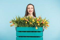 Belle boîte femelle de participation de jardinier avec des tulipes sur le fond bleu image stock