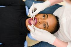Belle bouche femelle noire ethnique afro-américaine d'ouverture tandis que dentiste en état de contrôle blanc de gants de latex d images stock