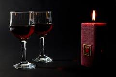 Belle bougie rouge et deux tasses en verre de vin rouge d'isolement sur le noir Photographie stock