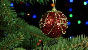Belle boule rouge de Joyeux Noël et de bonne année accrochant sur l'arbre sur des guirlandes d'un fond clips vidéos