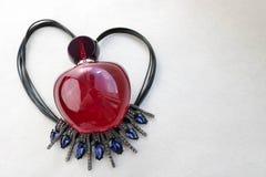 Belle bouteille transparente en verre rouge de parfum femelle se trouvant sur la ficelle noire sous forme de coeur décoré d'un bl Photos libres de droits