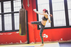 Belle boxe de fille contre le sac de sable (intentionnellement blurre photo libre de droits
