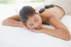 Belle brune appréciant un massage en pierre chaud Photo libre de droits