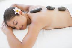 Belle brune appréciant un massage en pierre chaud Image libre de droits