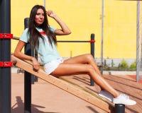 Belle brune aux longues jambes bronzée dans les shorts blancs et un T-shirt de turquoise se reposant sur une séance d'entraînemen Images stock