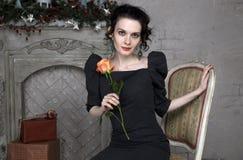 Belle brune avec une rose se reposant sur une chaise près de la cheminée Photo libre de droits
