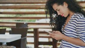 Belle brune bouclée utilisant le smartphone sur la terrasse d'été banque de vidéos