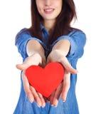 Belle brune d'amour et de Saint-Valentin tenant un coeur rouge dans des mains d'isolement sur le fond blanc Photo stock