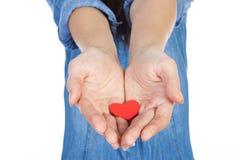 Belle brune d'amour et de Saint-Valentin tenant un coeur rouge dans des mains d'isolement sur le fond blanc Photographie stock