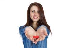 Belle brune d'amour et de Saint-Valentin tenant un coeur rouge dans des mains d'isolement sur le fond blanc Photo libre de droits