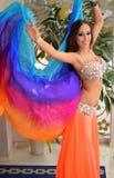 Belle brune, danseuse du ventre avec le châle d'arc-en-ciel dans l'intérieur arabe de harem Photographie stock libre de droits
