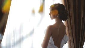 Belle brune de jeune mariée dans une longue robe de mariage dans un intérieur classique Matin de la jeune mariée banque de vidéos