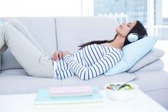 Belle brune de sourire détendant sur le divan et la musique de écoute photo libre de droits