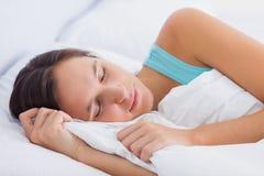 Belle brune dormant paisiblement dans le lit Photo stock