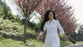 Belle brune heureuse dans la promenade blanche de robe en parc de floraison banque de vidéos