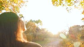 Belle brune marchant le long du parc d'automne et regardant autour Rayons lumineux du soleil Plan rapproché banque de vidéos