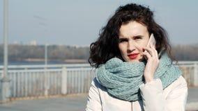 Belle brune parlant au téléphone et louchant du soleil lumineux banque de vidéos