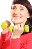 Belle brune pendant l'exercice de forme physique avec des haltères Photos libres de droits