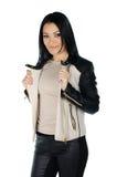 Belle brune posant et montrant son manteau en cuir Photos libres de droits