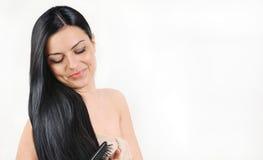 Belle brune s'inquiétant de ses cheveux lumineux forts, beau de station thermale Photographie stock