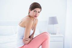 Belle brune souffrant de la douleur abdominale Images stock
