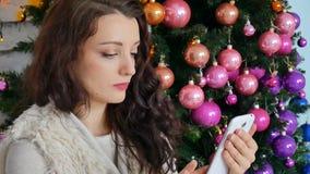 Belle brune sur le fond d'un arbre de Noël décoré poussant des feuilles par le menu dans son smartphone contrôles clips vidéos
