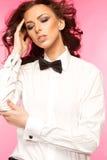 Belle brune utilisant un arc de lien noir et une chemise blanche Photographie stock
