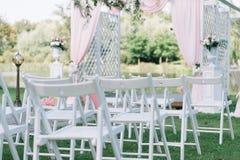Belle cérémonie de mariage d'été dehors Support décoré de chaises sur l'herbe Voûte de mariage faite de tissu léger et blanc et p Photos libres de droits