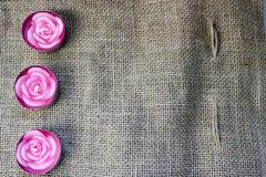 belle candele della cera rosa sotto forma di fiori rosa con uno stoppino non cotto sui precedenti di vecchia tela marrone, duri,  immagine stock