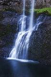 Belle cascade à gradins cascadant au-dessus des roches avec un refection bleu éthéré doux de ton dans l'eau Photos libres de droits
