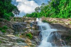 Belle cascade à la montagne avec le ciel bleu et les cumulus blancs Cascade en cascade verte tropicale de forêt d'arbre photographie stock libre de droits