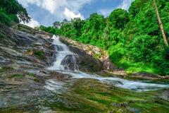 Belle cascade à la montagne avec le ciel bleu et les cumulus blancs Cascade en cascade verte tropicale de forêt d'arbre image stock