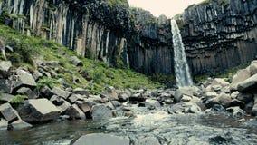 Belle cascade parmi les collines vertes en Islande banque de vidéos