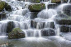 Belle cascate della cascata sopra le rocce in foresta Fotografia Stock Libera da Diritti