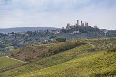 Belle colline con le vigne in Toscana con la città San Gimignan fotografia stock libera da diritti