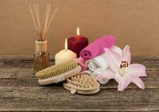 Belle composition avec deux bougies, huile aromatique et brosses de massage sur le fond en bois Image libre de droits