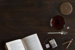 Belle confortablement configuration plate de tasse de thé, de livre, de biscuit et d'épices sur le plancher en bois photo libre de droits