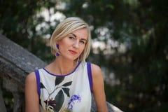 belle construction blonde derrière ses jeunes modernes de femme d'extérieur Image stock