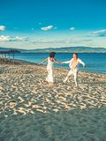 Belle coppie adorabili felici di nozze di giovane paople che si tengono per mano condizione all'acqua della costa e di ballare de fotografia stock