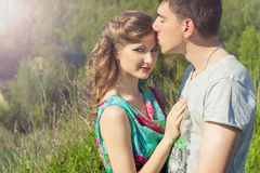 Belle coppie amorose dei tipi e delle ragazze nell'uomo di camminata del campo che bacia la fronte della ragazza Immagini Stock Libere da Diritti