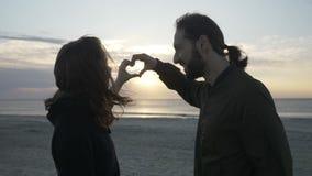 Belle coppie che godono del tramonto sul tenersi per mano baciante della spiaggia e che fanno un cuore da modellare al rallentato archivi video