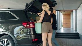 Belle coppie che prendono i sacchetti della spesa dal garage dell'automobile a casa video d archivio