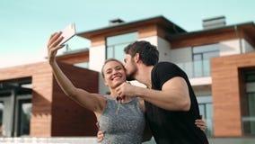 Belle coppie che prendono selfie con le chiavi della casa fuori della residenza stock footage